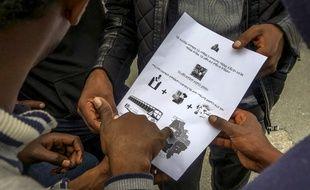Des demandeurs d'asile lisent un document rédigé en langue Tigrinya pour leur indiquer le lieu de leur centre d'hébergement.