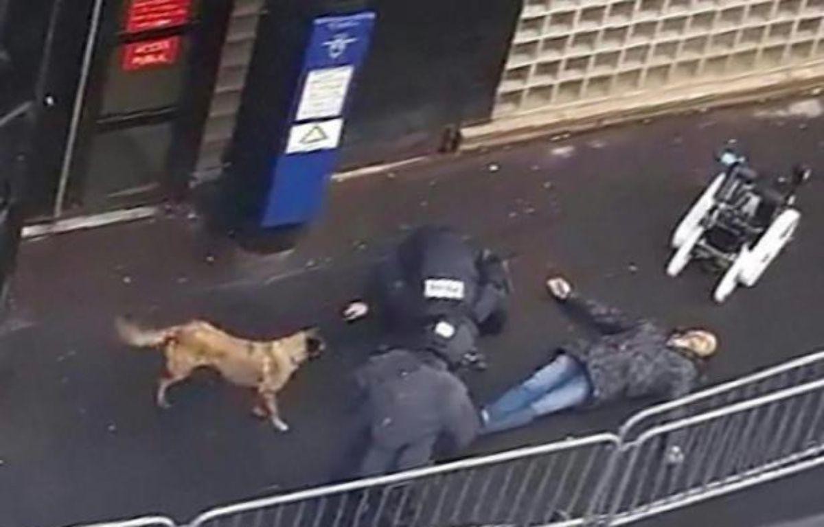 Une capture d'écran d'une vidéo obtenue par l'AFP montre la police et un robot démineur autour du cadavre d'un homme abattu par la police devant le commissariat de la Goutte-d'Or à Paris, le 7 janvier 2016 – STRINGER AFP
