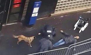 Une capture d'écran d'une vidéo obtenue par l'AFP montre la police et un robot démineur autour du cadavre d'un homme abattu par la police devant le commissariat de la Goutte-d'Or à Paris, le 7 janvier 2016