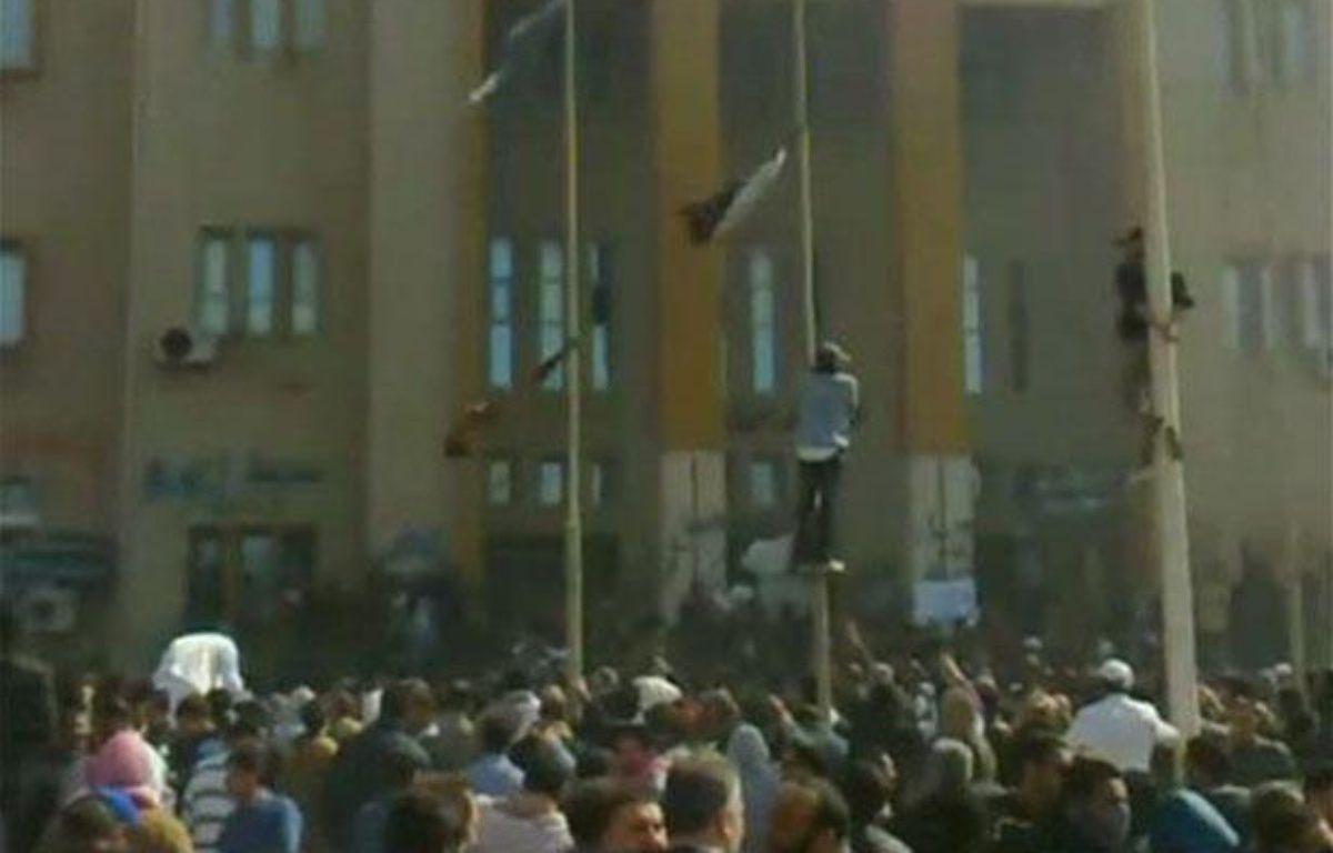 Des manifestants grimpent sur des poteaux devant un bâtiment de la sécurité intérieure à Benghazi, en Libye, le 20 février 2011. – REUTERS/Youtube