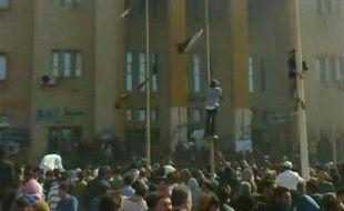 Des manifestants grimpent sur des poteaux devant un bâtiment de la sécurité intérieure à Benghazi, en Libye, le 20 février 2011.
