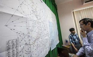 Un officiel vietnamien regarde une carte avec les détails des recherches en cours pour retrouver le Boeing 777, sur l'île de Pho Quoc le 11 mars 2014