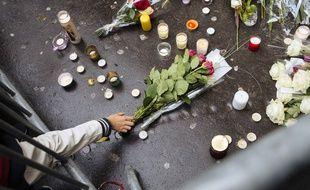 Des passants rendent hommage aux victimes des attentats du 13 novembre 2015 devant le Bataclan