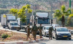 Des soldats israéliens fouillent des véhicules à l'entrée de la colonie d'Ariel, en Cisjordanie, le 24 décembre 2015