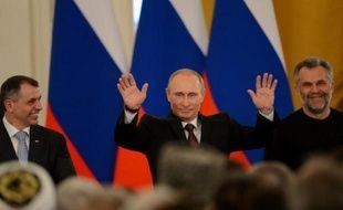Le président russe Vladimir Poutine (c) après la signature du traité rattachant la Crimée à la Russie au Kremlin à Moscou le 18 mars 2014