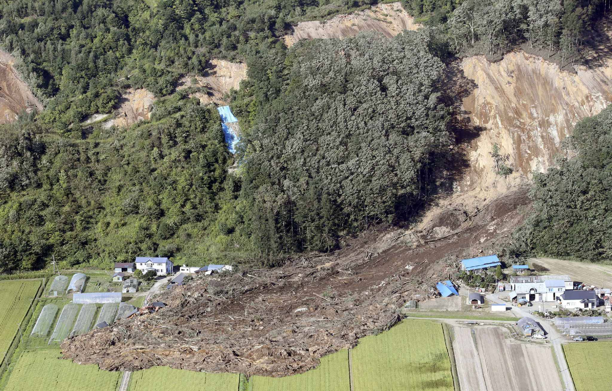 An aerial photo shows houses covered with landslide in Atsuma Town, Hokkaido on Sep.6, 2018. Severe earthquake registering 7 on the Japanese seismic scale in Atsuma Town, Iburi district of Hokkaido occurred at a.m. 3 on September 6th. According to the Meteorological Agency, the depth of the epicenter was estimated to be about 37 kilometers, and the indicative magnitude was estimated to be 6.7.