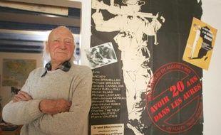 """Le cinéaste français René Vautier, pose à côté de l'affiche de son film anticolonialiste de 1948 """"Avoir 20 ans dans les Aurès"""", le 13 février 2008 à son domicile de Cancale"""