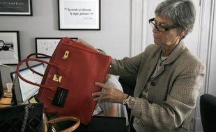 Dominique Chombert expertise un sac dans les locaux d'Instant Luxe, le 30 juillet 2014 à Paris