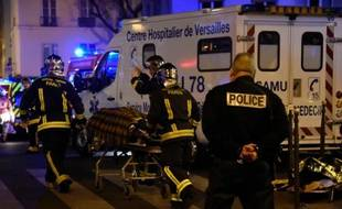 Des pompiers évacuent une personne blessée lors de l'attaque terroriste contre la salle du Bataclan, le 13 novembre 2014 à Paris