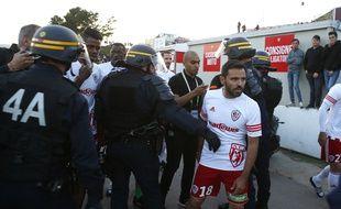 Le capitaine de l'AC Ajaccio Yohann Cavalli entouré par des CRS.
