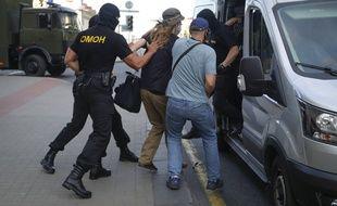 Un homme est arrêté par au moins deux policiers anti-émeutes, samedi, à Minsk.
