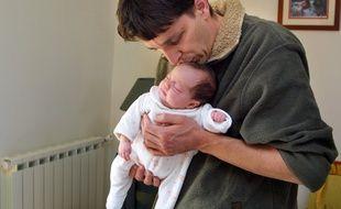 Un jeune papa avec sa fille, ici en 2002, lors de l'institution du congé paternité. (archives)