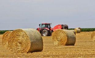 Un tracteur dans un champs de balles de paille. Illustration.