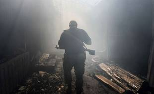 Un rebelle pro-russe dans un marché pilonné de Donetsk en Ukraine.