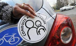 Une personne montre, le 13 janvier 2009 à Caen, un autocollant à apposer sur le véhicule d'un jeune conducteur en «conduite accompagnée».