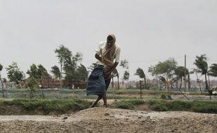Un homme essaie de lutter contre le vent à Bhadrak en Inde.