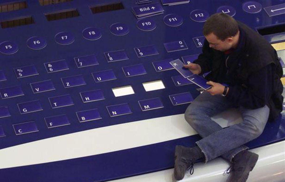 Un homme réassemble les lettres d'un clavier géant, à Hanovre (Allemagne), en février 2000. – REUTERS/Peter Mueller