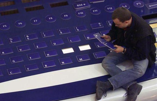 Un homme réassemble les lettres d'un clavier géant, à Hanovre (Allemagne), en février 2000.