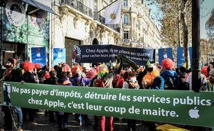 Des militants d'Attac ont manifesté dimanche 18 novembre 2018 lors de l'inauguration de l'Apple Store sur les Champs-Elysées à Paris.