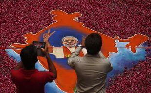 Des Indiens photographient le portrait de Modi, vainqueur des législatives, le 16 mai 2014.