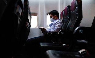 Un homme portant un masque de protection contre le Covid-19 à bord d'un avion. (illustration)