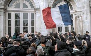 Un groupe agite le drapeau français en soutien au général Christian Piquemal, accusé d'avoir participé à une manifestation interdite contre les migrants, devant le tribunal de Boulogne-sur-Mer, le 8 février 2016