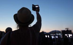 Une jeune femme filme avec son smartphone, ici lors d'un festival à Carhaix.