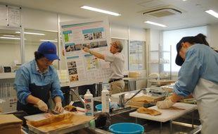Des employés du port d'Onahama préparent le poisson pour les tests de radiations, dans le département d'Iwaki, le 27 juillet 2018.