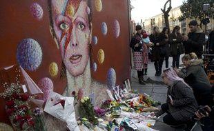 Des fans de David Bowie fleurissent un mur décoré d'un dessin en hommage au chanteur.