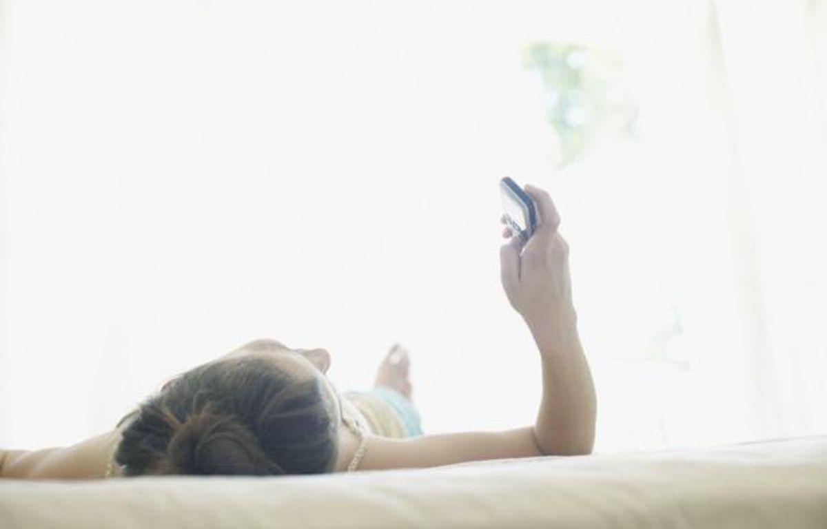 Femme sur un lit avec un téléphone. – OJO Images / Rex Features