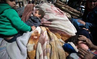 Des Syriens tentent de fuir leurs maisons dans la ville de Hamouria, dans la région assiégée de la Ghouta, le 4 mars 2018, à la suite de raids aériens. AFP PHOTO / ABDULMONAM EASSA