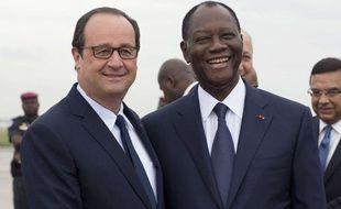 Le président français François Hollande serre la main de son homologue ivoirien, Alassane Ouattara, à son arrivée à Abidjan, le 17 juillet 2014.