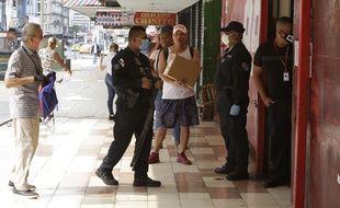 La police surveille l'entrée des supermarchés à Panama City, le 31 mars 2020.