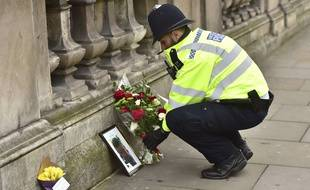 A police officer places flowers and a photo of fellow police officer Keith Palmer, who was killed in yesterdays attack, on Whitehall near the Houses of Parliament in London, Thursday March 23, 2017. On Wednesday a knife-wielding man went on a deadly rampage, first driving a car into pedestrians then stabbing a police officer to death before being fatally shot by police within Parliament's grounds in London.