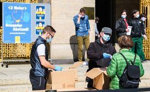 Distribution de masques à Dresde, en Allemagne.