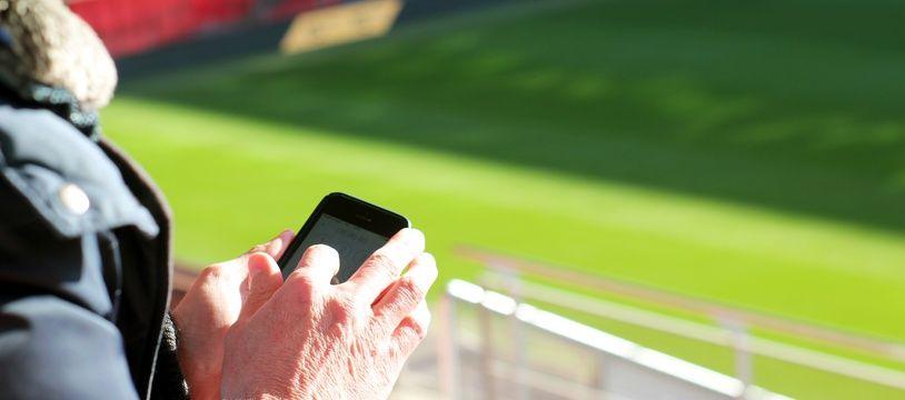Illustration d'un homme utilisant son smartphone au Roazhon Park, l'antre du Stade Rennais.