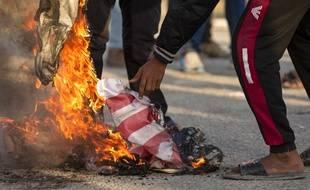 Des Irakiens brûlent un drapeau américain, le 30 décembre 2019 à Bassora en Irak.
