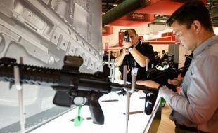 Des visiteurs inspectent des armes Sig Sauer, pistolets et fusils semi-automatiques, durant un salon de l'équipement de défense et de sécurité à Londres le 15 septembre 2015