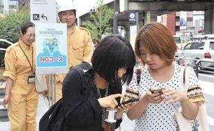 Deux Japonaises utilisent Twitter pour partager des informations lors d'un exercice de simulation de catastrophe naturelle à Tokyo, en septembre 2012.