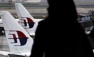 Une femme regarde des appareils de la Malaysia Airlines, le 26 mars 2014 à Kuala Lumpur.