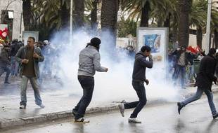 Des manifestants courent au milieu des gaz lacrymogènes à Tunis, le 6 février 2013.