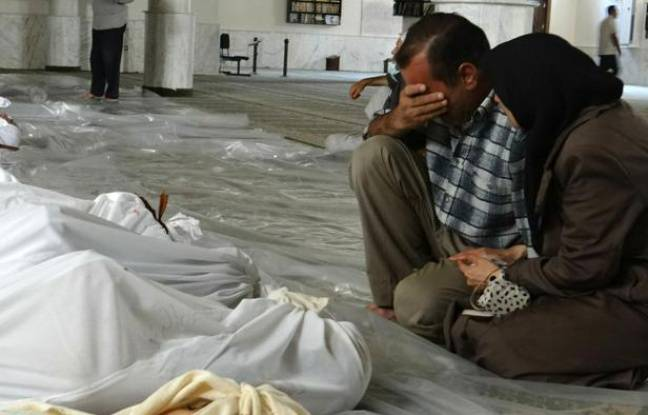 Photo fournie par le réseau d'opposition syrienne Shaam News montrant un  couple pleurant face aux cadavres de proches, tués lors d'une attaque  qui pourrait être d'origine chimique, le 21 août 2013 près de Damas