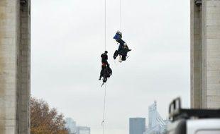"""Des officiers de police arrêtent des activistes de Greenpeace après avoir brandit une affiche """"Mr Hollande, renouvelez l'énergie"""" , le 11 décembre 2015 à Paris"""