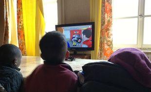 De jeunes enfants d'origine africaine devant les dessins animés à la télévision à Thal-Marmoutier où ces familles de réfugiés préparent leur installation en France. Illustration
