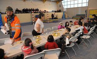 Des employés d'ONG donnent à manger aux enfants d'un groupe de 124 clandestins débarqués sur une plage, le 22 janvier 2010 à Bonifacio.