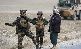 Un commandant de la police afghane discute avec un gendarme français sur la route d'Axe Vermont (province de Kapisa) où deux journalistes français ont été enlevés le 30 décembre 2009 (photo prise le dimanche 3 janvier 2010).
