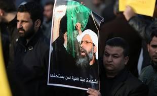 Un homme tient une pancarte représentant l'émir exécuté lors d'une manifestation à Bagdad en Irak.