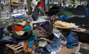 Des bénévoles récupèrent les tentes en bon état lors de l'évacuation d'un campement de migrants le 16 juin 2016 à Paris