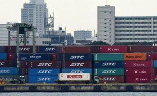 Un camion passe à côté d'une pile de conteneurs dans un port de Tokyo le 8 décembre 2015
