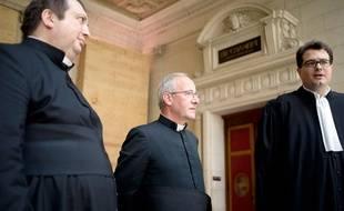 Le curé de Saint-Eloi Yannick Vella, l'abbé de l'Institut du Bon Pasteur Philippe Laguerie, et leur avocat, au palais de justice de Paris le 11 septembre 2014.